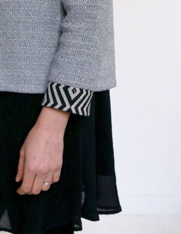 Claudie jacket in black and white thick cotton, with no collar, focus on wrist made in an other fabric with geometrical drawing
